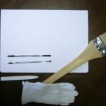 Herramientas para el trabajo de conservación: carpeta libre de ácido, brocha, espátulas, plegadera y guantes de algodón