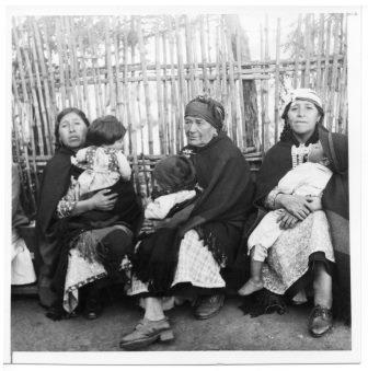 Mujeres mapuche sosteniendo niños en brazos