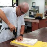 El contratista Steve Fonseca Fernández perfora con un taladro el lomo de los expedientes de índices notariales.