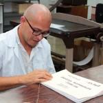 El contratista Steve Fonseca Fernández cose con hilo, amarra el hilo del cosido y corta el hilo de los expedientes de índices notariales.