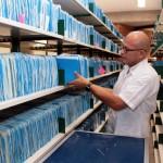 El contratista Steve Fonseca Fernández revisa y traslada al Departamento de Conservación los expedientes de índices notariales para prepararlos.